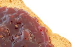 Inceppamento dorato di lampone e della fetta biscottata Fotografia Stock