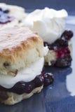 Inceppamento e focaccina al latte crema fresca sul piatto blu Immagine Stock