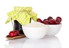 Inceppi il barattolo, le ciliege della tazza, lo zucchero, cucchiaio di legno con le bacche isolate Fotografia Stock