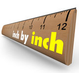Inch by Inch Incremental Growth Increasing Ruler Measure. The words Inch by Inch on a wooden ruler to measure your incremental growth, increase or length Royalty Free Stock Image