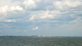 Inchamento o Mar Negro com ondas, o litoral com construções da cidade na distância e o céu bonito vídeos de arquivo
