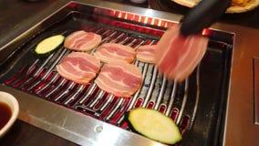 Inche a carne de porco que está sendo posta sobre um assado coreano vídeos de arquivo