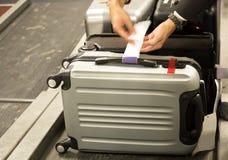 Incheckninganställd fäster en bagageetikett till resväskan av passenge Royaltyfri Fotografi