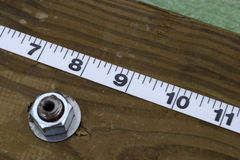Inches. Close up of a section of measuring tape on a piece of lumber along with a bolt and nut Royalty Free Stock Photography