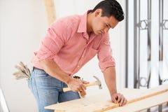 Inchiodare legno con un martello Fotografia Stock Libera da Diritti