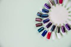 Inchiodi i campioni, grande raccolta delle unghie del dito in vario colore su fondo pastello Chiuda sulla tavolozza degli smalti  fotografia stock