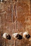 inchiodi la pittura spogliata sporca nella porta di legno marrone e nel rosso arrugginito Fotografie Stock
