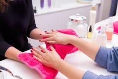 Inchiodi le mani asciutte del salone con l'asciugamano dopo il bagno di rinnovamento della pelle Fotografie Stock Libere da Diritti