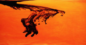 Inchiostro nero in acqua arancio Fotografia Stock Libera da Diritti
