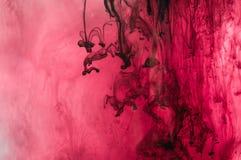Inchiostro rosso, rosa, nero, bianco in acqua Illuminazione del sole dinamico Fotografia Stock