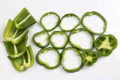 Incida i peperoni verdi dei pezzi su fondo bianco Fotografia Stock Libera da Diritti