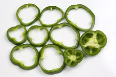 Incida i peperoni verdi dei pezzi su fondo bianco Fotografia Stock