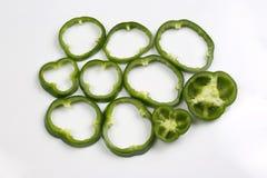 Incida i peperoni verdi dei pezzi su fondo bianco Immagine Stock