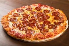 Incida i pezzi di salsiccia e di formaggio della pizza su un vassoio di legno immagini stock libere da diritti