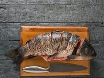 Incida il pesce della carpa dei pezzi con un coltello su una tavola nera Posto per il vostro testo fotografia stock