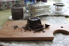 Incida il piccolo cioccolato fondente dei pezzi sul bordo di legno Fotografie Stock
