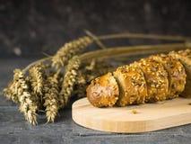 Incida le fette di baguette su un tagliere su una tavola di legno Immagini Stock