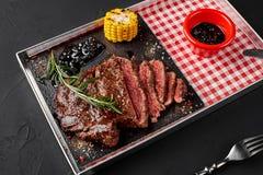 Incida parecchi pezzi di filetto di manzo arrostito con le erbe, il mais al forno e la salsa del rosmarino-ribes Vista superiore Fotografia Stock