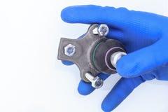 Incidence sphérique un des éléments dans la suspension de la voiture monté sur le levier le maître dans les gants bleus tient le  photo libre de droits