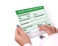 Incident or accident report form on tablet computer. Doctor holding tablet computer in hand that show the report form of Incident or accident information on royalty free stock photo