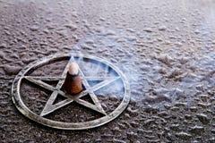 Incienso ardiente en el centro del pentagram gris del metal en backg de la pizarra imagen de archivo