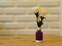 Incienso del aroma con flores plásticas con el backg blanco de la pared de ladrillo foto de archivo