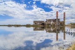 Incinérateur avec des cheminées près d'une lagune Photo stock