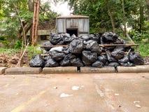 Incinérateur de jardin avec les sacs noirs Photo stock