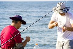 Two fishermen are preparing their fishing rods Royalty Free Stock Photos