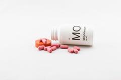 Incliné au-dessus de la bouteille de vitamines de molybdène Photos libres de droits