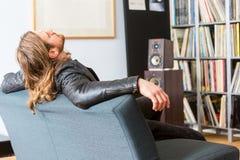 Inclinação Audiophile para trás em um sofá que escuta a música imagens de stock