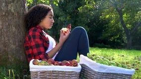 Inclinação de assento da jovem mulher afro-americano Biracial do adolescente da raça misturada contra uma árvore em um pomar que  vídeos de arquivo