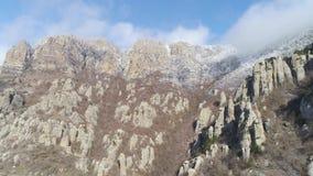 Inclinação de montanha íngreme com os pedregulhos enormes, cobertos por arbustos congelados contra o céu azul nebuloso bonito no  vídeos de arquivo