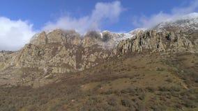 Inclinação de montanha íngreme contra o céu azul nebuloso bonito, coberto por arbustos congelados com as formações de rocha estra filme