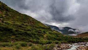 inclinação de montanha na nuvem de encontro com as coníferas sempre-verdes encobertas na névoa em uma opinião cênico da paisagem Fotografia de Stock