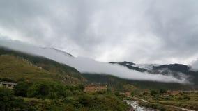 inclinação de montanha na nuvem de encontro com as coníferas sempre-verdes encobertas na névoa em uma opinião cênico da paisagem Fotografia de Stock Royalty Free