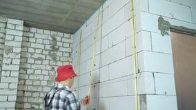 Inclinação disparada do construtor que instala os trilhos do metal nas braçadeiras na parede do bloco video estoque