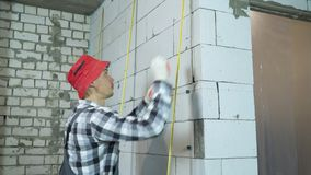 A inclinação disparou acima do construtor que instala as braçadeiras na parede ventilada do bloco de cimento vídeos de arquivo