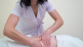 A inclinação disparou acima do massagista fêmea que faz massagens o abdômen da jovem mulher video estoque