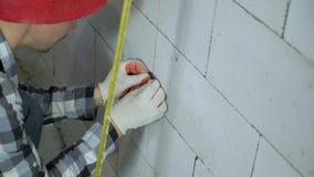A inclinação disparou acima do trabalhador da construção que instala as braçadeiras na parede do bloco filme