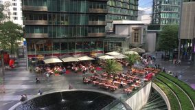 Inclinação do telhado nos povos que apreciam restaurantes e serviços em Potsdamer Platz Sony Center com a fonte no meio vídeos de arquivo