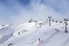 Inclinação nevado e esqui-elevador do esqui na estância de esqui no eveni ensolarado do inverno foto de stock