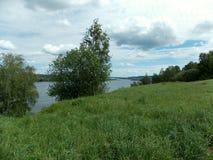Inclinação verde acima do rio Fotos de Stock Royalty Free