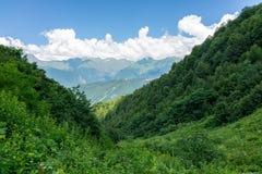 A inclinação verde das montanhas, descendo ao vale, cercado por montanhas altas foto de stock