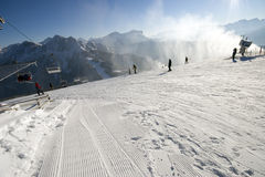 Inclinações do esqui em Áustria Cânone da neve na ação Dia de inverno ensolarado bonito Fotos de Stock