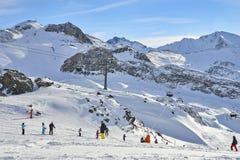 Inclinações do recurso e do esqui do inverno entre montanhas no fundo imagens de stock