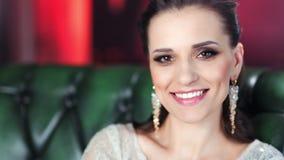 Inclinación encima de la muchacha sonriente hermosa de la moda del retrato con la cabeza elevadora del maquillaje de la tarde qu almacen de video
