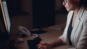 Inclinación-para arriba tirada de la mujer joven seria que trabaja en el ordenador que mecanografía y que mira la pantalla que se metrajes