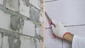 Inclinaison en bas du plan rapproché de la main de constructeur enlevant la mousse de montage excessive entre les murs banque de vidéos