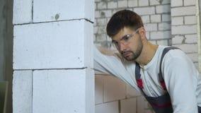 Inclinaison tirée du jeune constructeur dans le mur de meulage de bloc d'usage de travail avec l'outil abrasif banque de vidéos